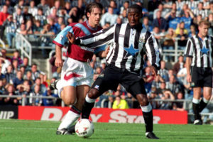 Newcastle United's Andy Cole (r) breaks away from West Ham United's Ian Bishop (l)